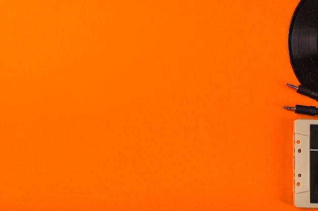 Primo piano del nastro a cassetta e disco in vinile su uno sfondo arancione