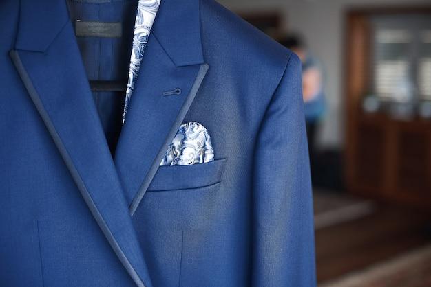Primo piano del nuovo vestito blu e cravatta dello sposo appeso su un gancio