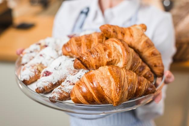 Primo piano del panettiere femminile vago che tiene croissant fresco nel vassoio