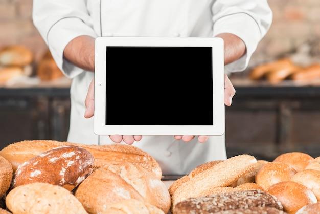 Primo piano del panettiere maschio che mostra compressa digitale in bianco sopra il pane al forno