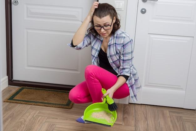 Primo piano del pavimento di pulizia della donna con la pentola della scopa e della polvere