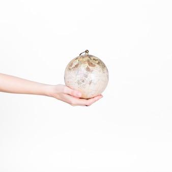 Primo piano del pendolo del globo della holding della mano di una persona su priorità bassa bianca