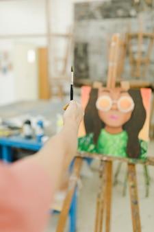 Primo piano del pennello della tenuta della mano della donna davanti a pittura sul cavalletto