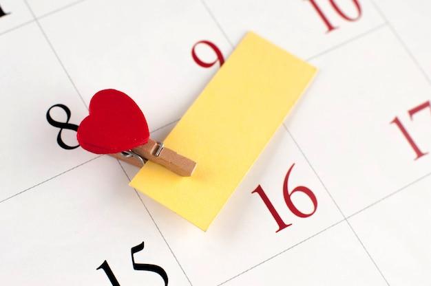 Primo piano del perno di legno con il cuore sulla pagina del calendario