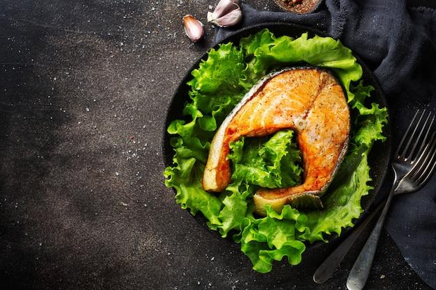 Primo piano del pesce di color salmone al forno con insalata verde