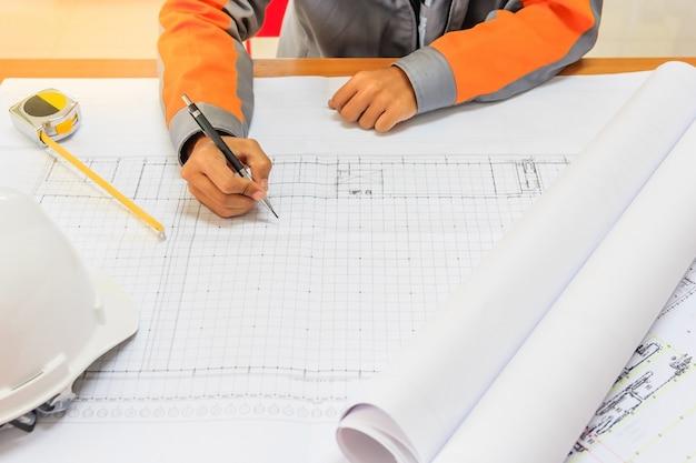Primo piano del piano di disegno della mano della persona su blue print con l'attrezzatura dell'architetto.