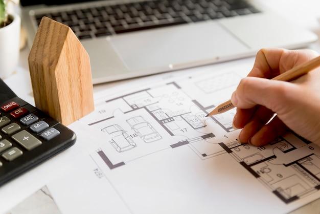 Primo piano del piano di disegno della mano della persona sulla stampa blu con il computer portatile; modello di casa e calcolatrice
