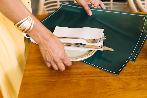 Primo piano del piatto della holding della mano della donna; posate e tovaglietta dal tavolo di legno