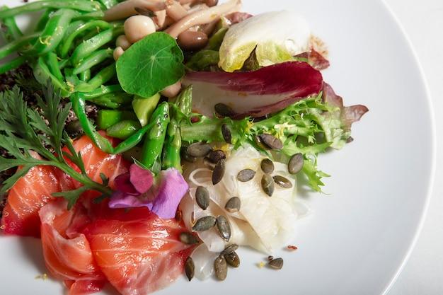 Primo piano del piatto di salmone marinato in barbabietola e aneto. fagiolini perona, finocchi sottaceto, asparagi verdi, funghi marinati e semi di zucca. immagine isolata