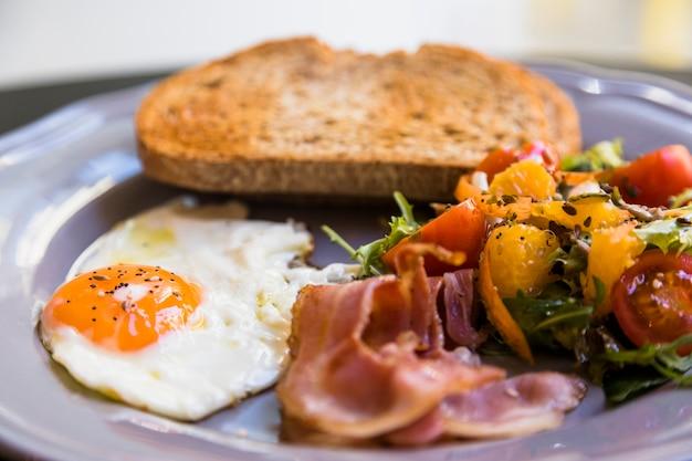 Primo piano del piatto grigio con pane tostato; uova fritte; pancetta e insalata