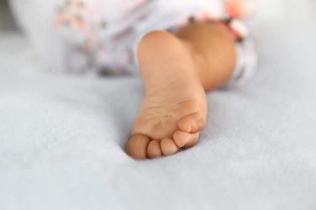 Primo piano del piede del bambino coperto su una morbida coperta, maternità e concetto di prima infanzia
