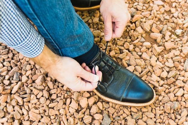 Primo piano del piede di un uomo su ciottolo che lega il laccio delle scarpe