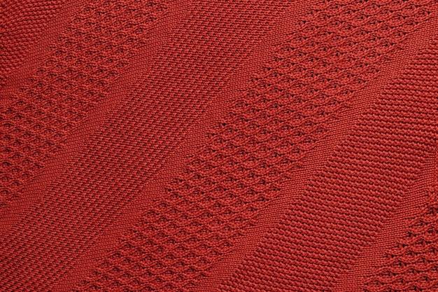 Primo piano del plaid lavorato a maglia rosso. trama a maglia con ornamento diagonale. sfondo caldo dettagliato fatto di filato.