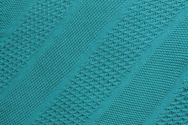 Primo piano del plaid lavorato a maglia turchese. trama a maglia con ornamento diagonale. sfondo caldo dettagliato fatto di filato.