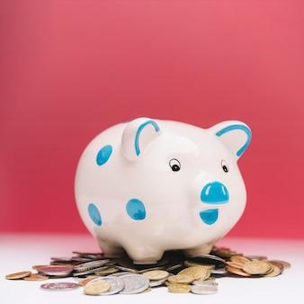 Primo piano del porcellino salvadanaio ceramico sopra le monete