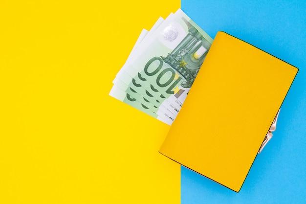 Primo piano del portafoglio giallo con 100 banconote in euro su un tavolo colorato