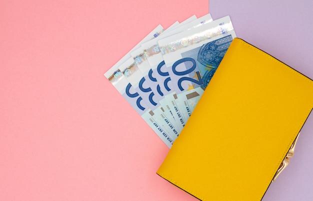 Primo piano del portafoglio giallo con le euro banconote su un fondo colorato