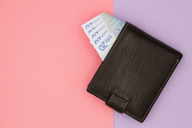 Primo piano del portafoglio nero con le euro banconote su un fondo colorato
