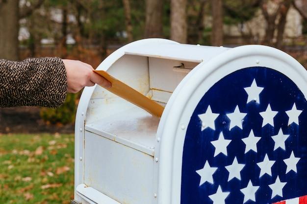 Primo piano del postino che mette la bandiera americana della cassetta delle lettere delle lettere