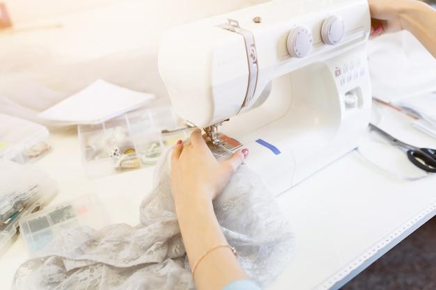 Primo piano del processo di cucitura, la macchina da cucire con le mani delle donne sarta