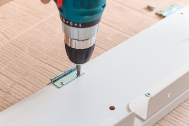 Primo piano del processo di installazione di un mobile con un cacciavite elettrico