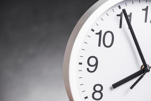Primo piano del quadrante dell'orologio su sfondo grigio