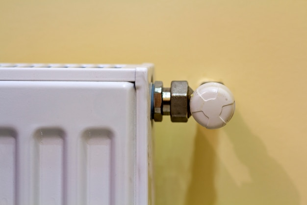 Primo piano del radiatore bianco del riscaldamento con la valvola del termostato sul fondo leggero dello spazio della copia della parete. comodo interno di casa calda, climatizzazione, concetto di risparmio di denaro.