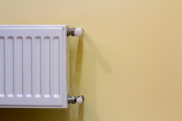 Primo piano del radiatore bianco del riscaldamento con la valvola del termostato sullo spazio leggero della copia della parete. comodo interno di casa calda, climatizzazione, concetto di risparmio di denaro.