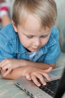 Primo piano del ragazzo biondo che per mezzo del computer portatile