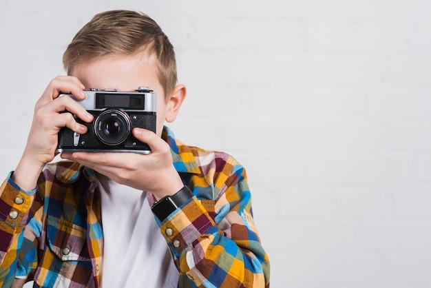 Primo piano del ragazzo che cattura maschera con la macchina fotografica dell'annata contro fondo bianco