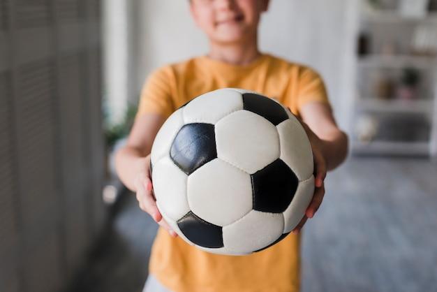 Primo piano del ragazzo che dà pallone da calcio verso la macchina fotografica