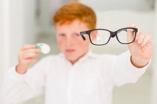 Primo piano del ragazzo che mostra gli occhiali neri della struttura