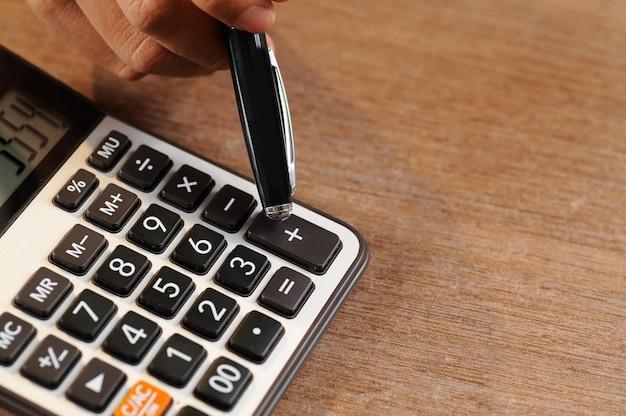 Primo piano del ragioniere che conta sul calcolatore