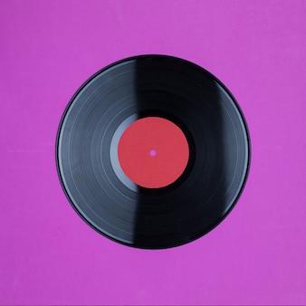 Primo piano del record del gioco lungo del vinile con l'etichetta con lo spazio della copia sulla parete rosa