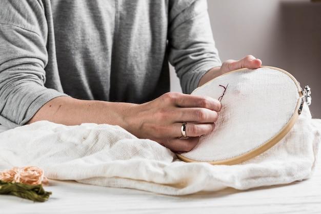 Primo piano del ricamo cucito a mano femminile su tessuto bianco