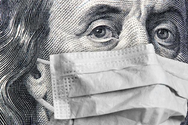 Primo piano del ritratto di benjamin franklin su una banconota da 100 dollari in una mascherina medica