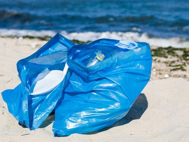 Primo piano del sacchetto di immondizia blu sulla sabbia alla spiaggia
