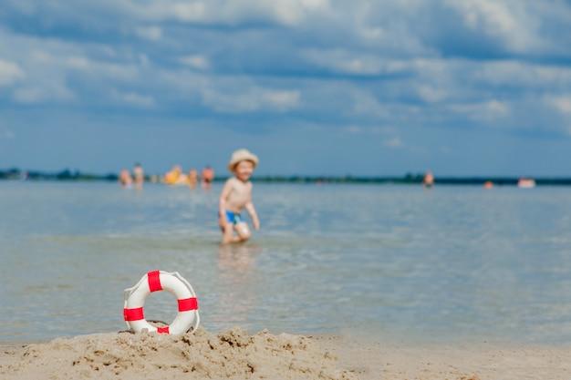 Primo piano del salvagente sulla spiaggia sul fondo del bambino. sicurezza sull'acqua.