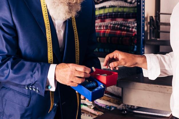 Primo piano del sarto maschio che mostra la bobina del filo al suo cliente
