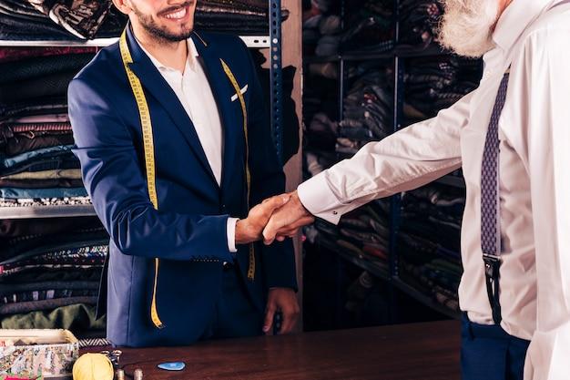 Primo piano del sarto maschio sorridente che stringe mano con il cliente senior