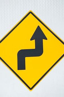 Primo piano del segno della freccia della strada della doppia curvatura