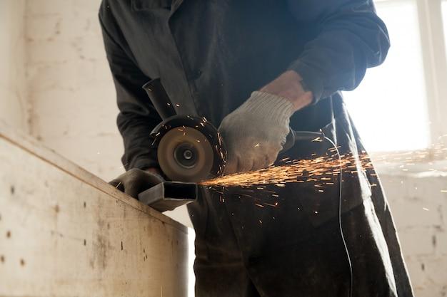 Primo piano del taglio del tubo di metallo, l'uomo usando smerigliatrice d'angolo