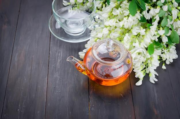 Primo piano del tè dell'acacia sulle tavole di legno
