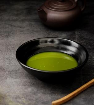 Primo piano del tè di matcha in ciotola con la teiera