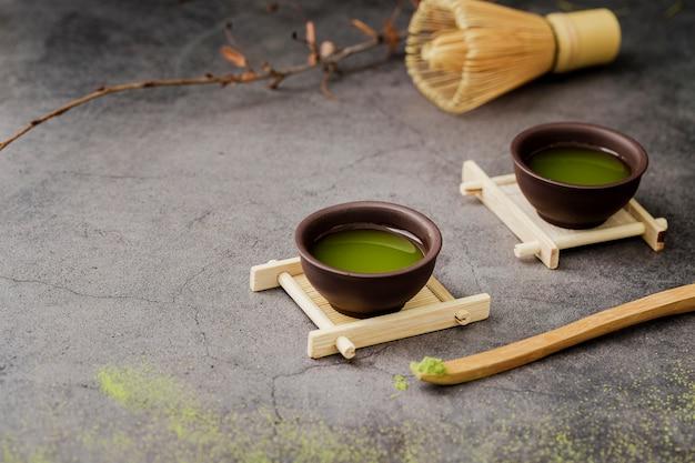 Primo piano del tè di matcha in tazze con lo spazio della copia