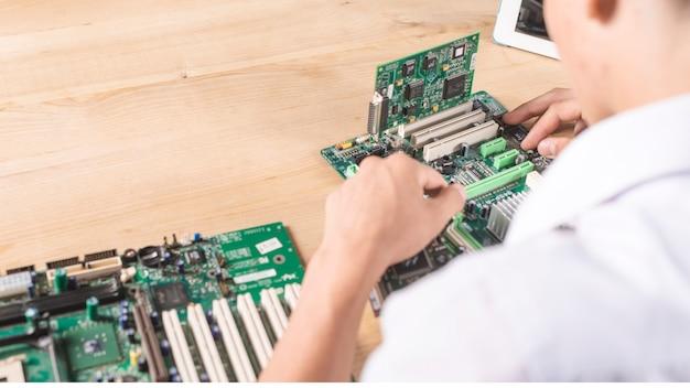 Primo piano del tecnico maschio che ripara la scheda madre moderna del pc sulla tavola di legno