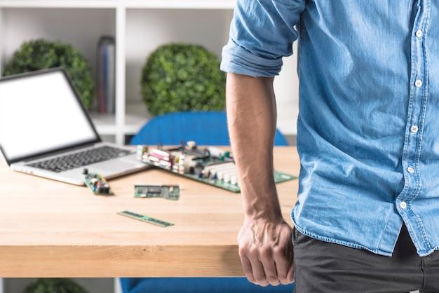 Primo piano del tecnico maschio che si appoggia al bordo della tabella con attrezzature del computer portatile e dell'hardware