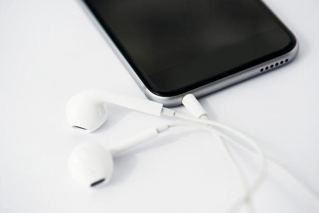 Primo piano del telefono cellulare con gli auricolari