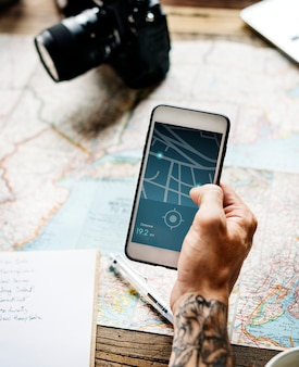 Primo piano del telefono cellulare della tenuta della mano del tatuaggio che mostra l'itinerario dei gps
