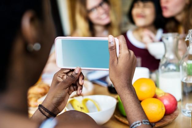 Primo piano del telefono cellulare prendendo foto di diverse donne